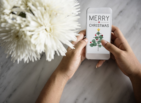 Woman holding a mobile phone with merry christmas concept