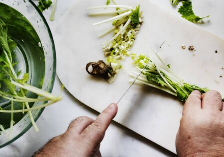 Closeup of hands with knife cutting fresh organic vegetable