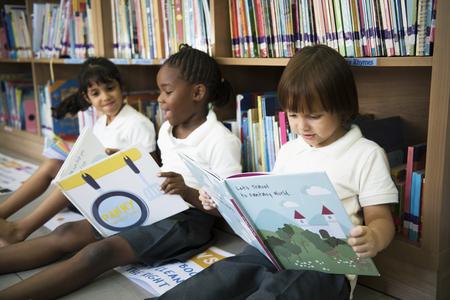 子供の物語の本を一緒に読んで多様な若い学生のグループ