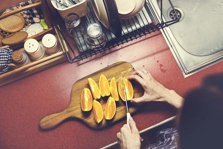 A sliced orange is on a wooden cutting board. 版權商用圖片