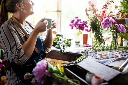 Woman takes coffee break at flower shop Stok Fotoğraf