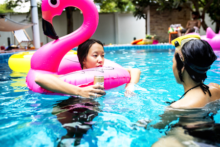 Asian women enjoying the pool with inflatable tubes