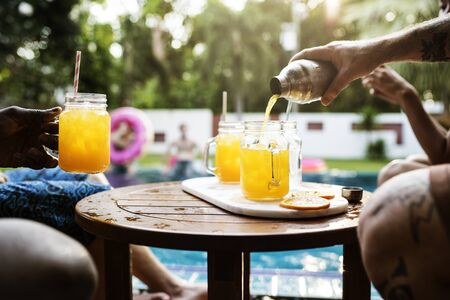 Hand pouring orange beverage to glasses by the pool Stock Photo
