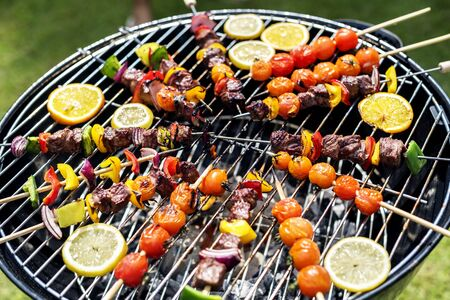Group of diverse friends grilling barbecue outdoors Stock Photo