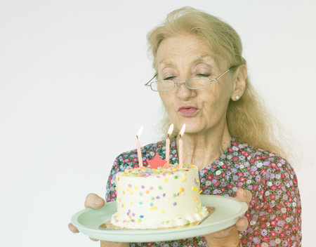 Senior Woman Hold Blowing Birthday Cake Studio Portrait