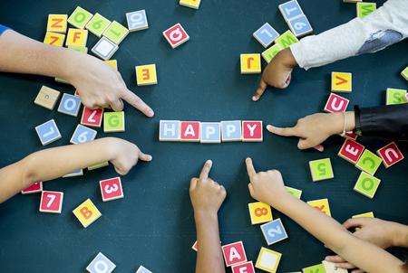 Kleuterschooljonge geitjes die houten de woordenschatspel van alfabettenbrieven spelen