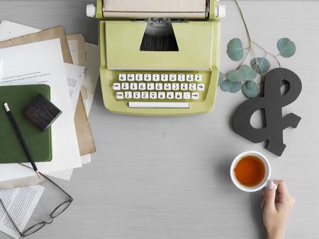 グレーのテーブルの上のティーカップを持つ手とレトロ タイプライター