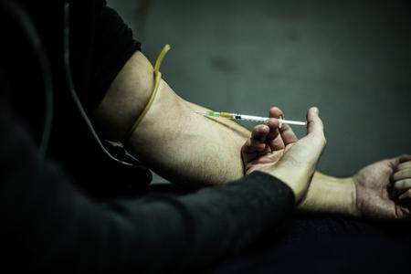 違法な麻薬を注入する注射器を使用して中毒の人々