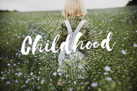 Childhood word on young boy outdoors Stock Photo