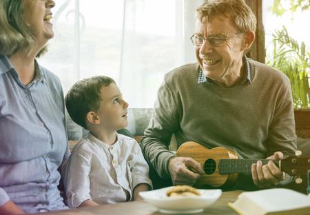 Happiness family playing leisure song with ukulele 版權商用圖片
