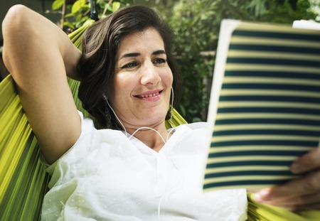 Woman lying on hammock chilling reading book Stock Photo