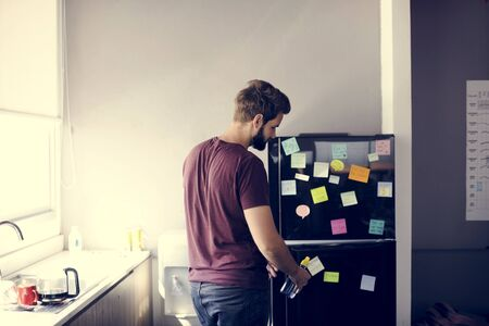 Man Taking Water Bottle From Fridge in Pantry Room During Break Time