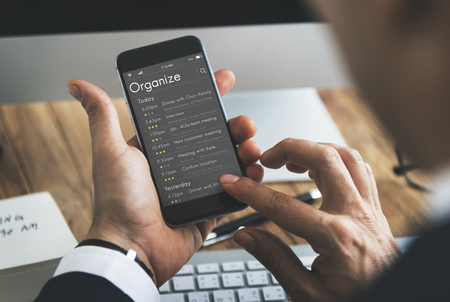 using smartphone: Man checking appointment on personal organizer schedule