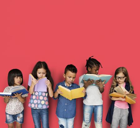 Grupo diverso de estudo de crianças Leia o livro Foto de archivo - 81724263