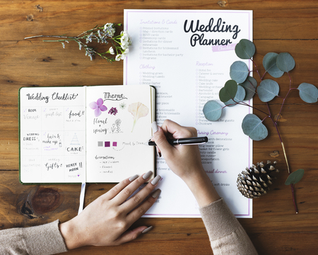 Hands Checking on Wedding Planner Notebook Banco de Imagens