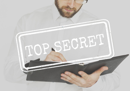 Businessman working and writing with top secret stamp Stock Photo