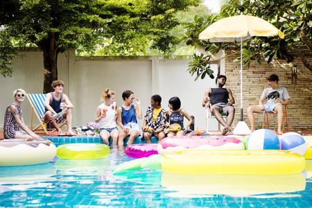 Groep diverse vrienden genieten van het zwembad met opblaasbare buizen Stockfoto