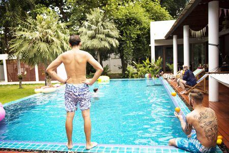 수영장 옆에 서있는 사람의 후면보기