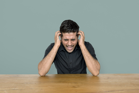 headaches: Stress man is sitting at wooden table