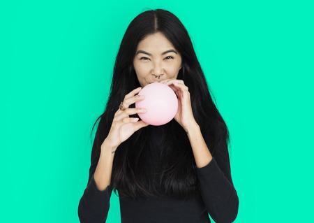 風船をふくらまして若いアジア女性カジュアル