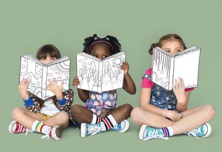 座って読む小さな子どもたち 写真素材