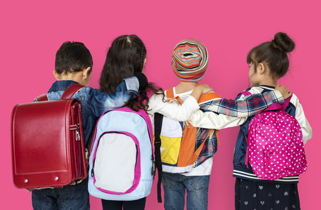 Rear view group of diverse kids wearing backpack Stock Photo