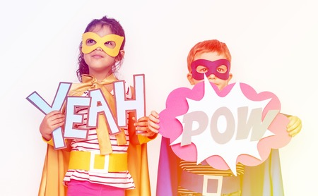 papercraft: Sister and brother holding papercraft yeah and pow word Stock Photo