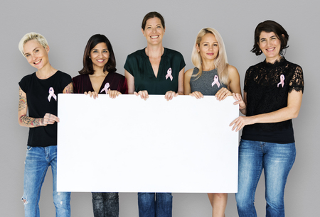 Group of women with pink ribbon and holding blank banner for breast cancer awareness Stock Photo - 81997316