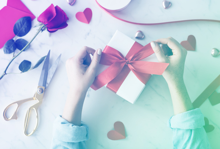 Hands tie ribbon on gift box Stock Photo