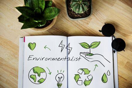 나무 테이블에 환경 스케치와 함께 펼쳐진 책 스톡 콘텐츠