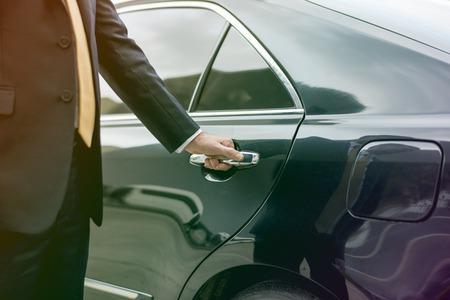 ビジネスマンのリムジン車のドアを開く 写真素材
