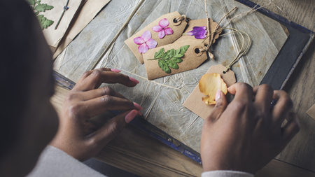 女性は、押し花アートを作成します。