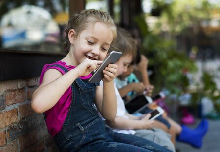 Children are using digital device together