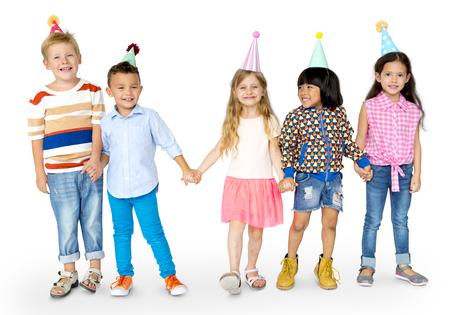 お祭り帽子パーティーの行に立って子供の多様なグループ 写真素材