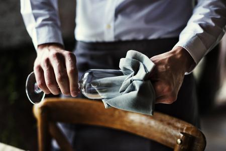 レストランのスタッフがレセプションのテーブル設定サービスでガラスを拭く