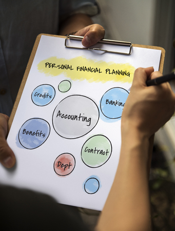 Person signing on a clipboard with personal financial planning concept