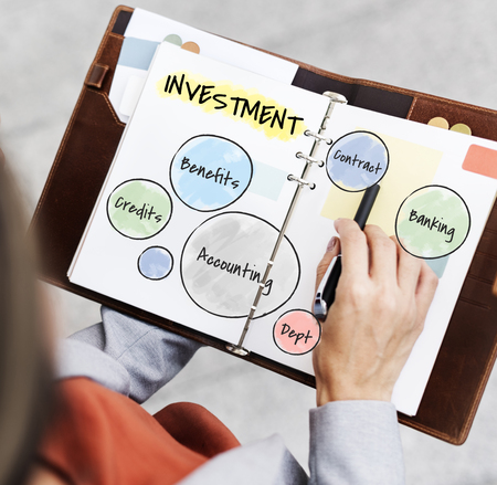 Woman holding a planner with investment concept Stock Photo