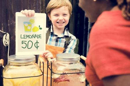 Pequeño muchacho que muestra el precio de la limonada en el mercado del establo de la comida Foto de archivo - 82102334