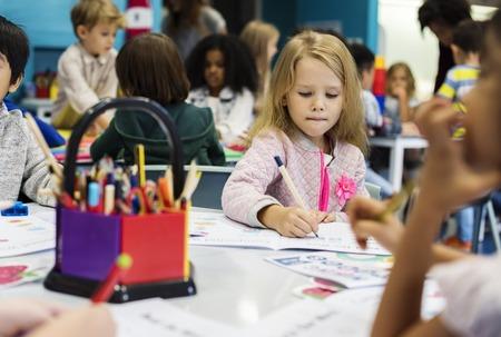 Groupe de divers enfants coloriage classeur en classe Banque d'images - 82102387