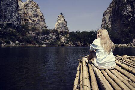배낭 여행자 여자는 호수에서 뗏목에있다.