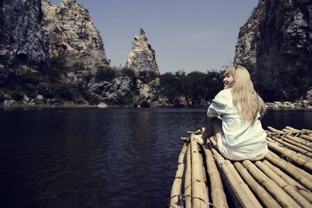 Backpack Traveler Woman is on a raft in a lake