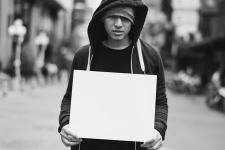 Asian man holding blank banner on the street