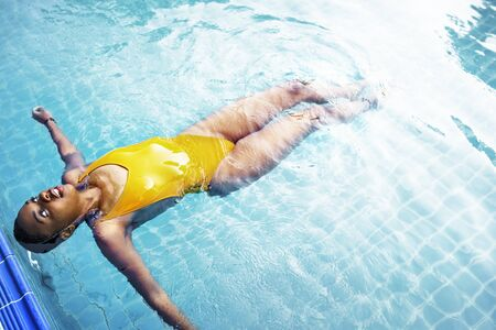resting: African descent girl floating in swimming pool
