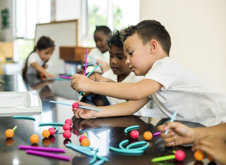 Diverse kindergarten students holding learning structures from toys