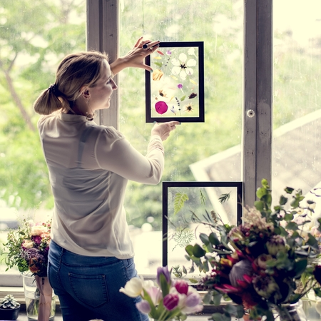 Florist woman holding frame of pressed flower