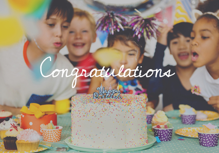 Group of diverse children blowing birthday cake together