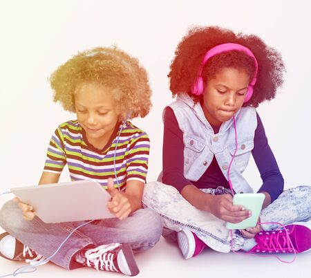Young kids using tablet and mobile to listen to music Stock Photo