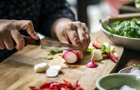 Hands using a knife chopping turnips Stock Photo