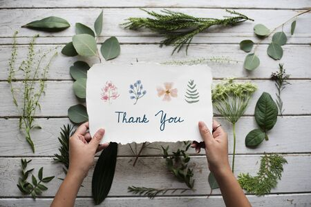 Hand Holding Show Thank You Card with Green Leaves Background