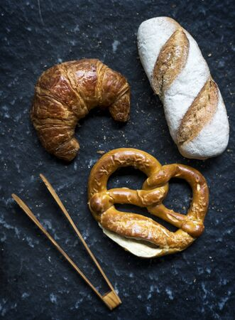 Croissant pretzel and baguette with wooden tongs 版權商用圖片